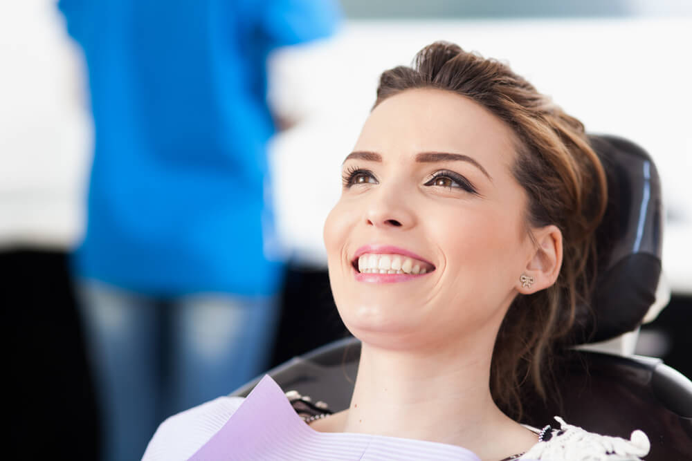 woman smiling in dental chair after oral screening